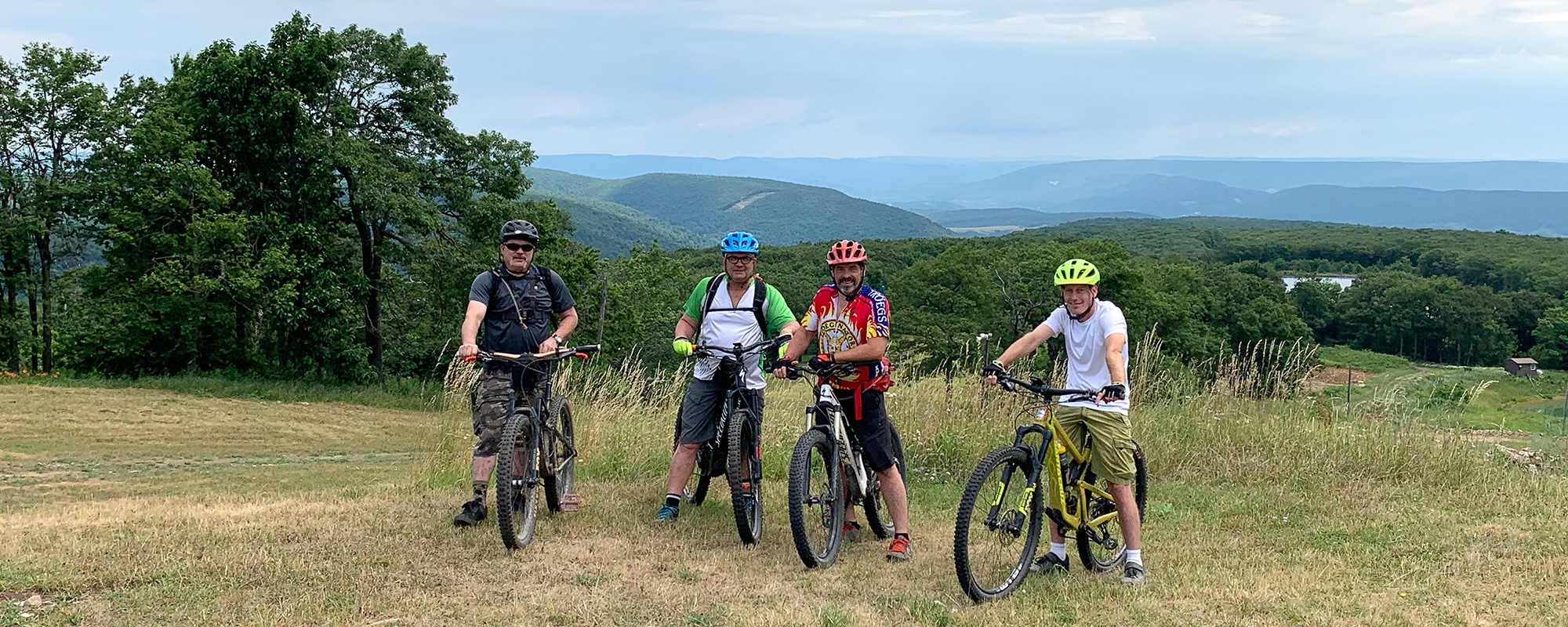 Mountain bikers stand on a grassy field atop a mountain