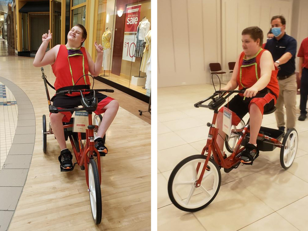 a happy boy rides an adaptive bicycle